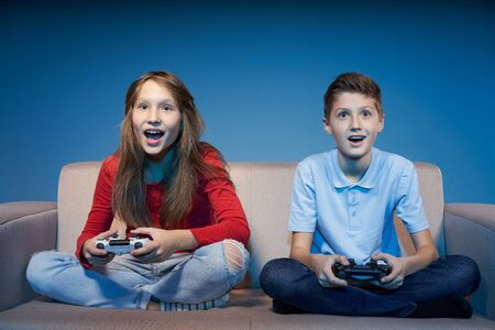 Computer game competition. Gaming concept. Excited children sitting on sofa playing video game with joysticks