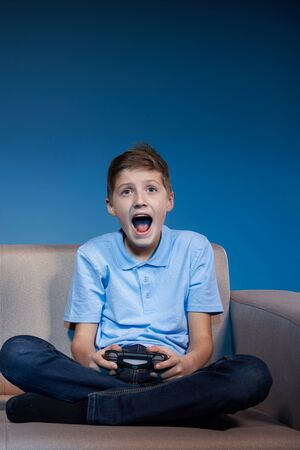 Computer game competition. Gaming concept. Excited boy sitting on sofa playing video game with joystick screaming 写真素材