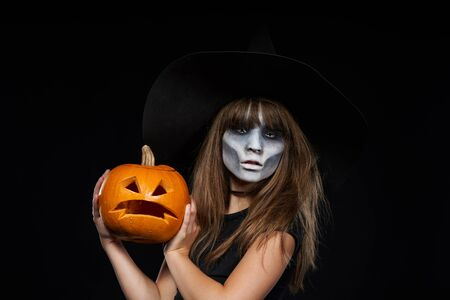 Serious Halloween witch holding Jack-O-Lantern pumpkin looking at camera on black background. Preteen girl with terrifying makeup and witch hat.