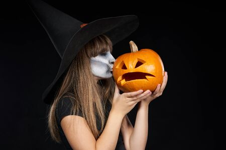 Halloween witch girl giving a kiss to Jack-O-Lantern pumpkin, on black background. Preteen girl with terrifying makeup and witch hat.