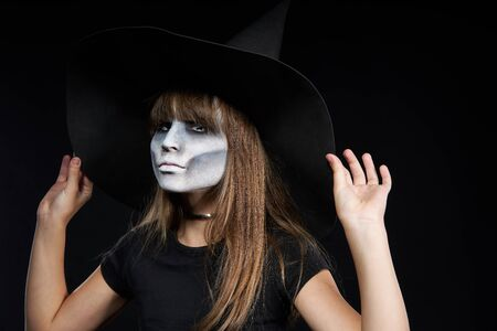 Closeup of Halloween witch girl adjusting her hat, looking at camera on black background. Preteen girl with terrifying makeup and witch hat.