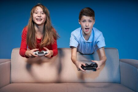 Computer game competition. Gaming concept. Excited children leaning on the sofa back playing video game with joysticks