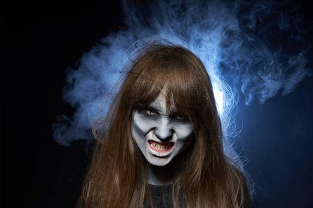 Halloweenowy zombie. Zbliżenie portret dziewczyny z makijażem zombie pokazując jej zęby na ciemnym tle z dymem i podświetleniem