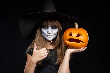 Chica bruja de Halloween mostrando calabaza Jack-O-Lantern en la palma y dando pulgar hacia arriba mirando a cámara sobre fondo negro. Niña preadolescente con maquillaje aterrador y sombrero de bruja. Foto de archivo