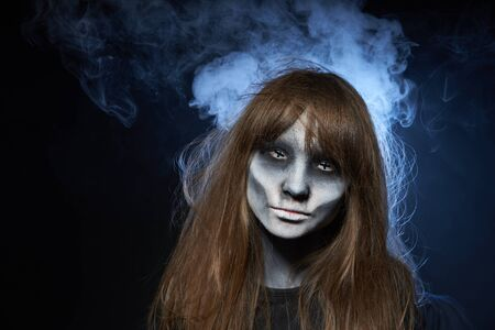 Halloween zombie. Closeup portrait of a girl with zombie makeup looking at camera over dark background with smoke and backlight