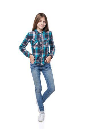 Full length teen girl in checkered shirt standing casually over white background