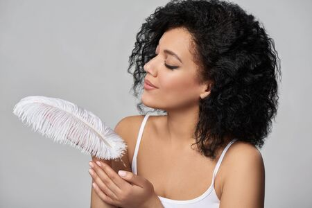 Closeup portrait of beautiful mixed race woman holding white ostrich feather on her palm enjoying its softness and beauty, studio shot