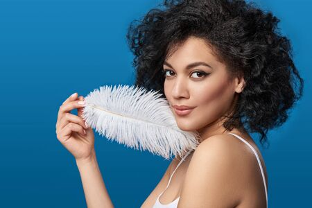 Closeup portrait of beautiful mixed race woman touching her skin with white ostrich feather looking at camera, studio shot over blue background