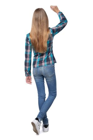 Full length back view of teen girl in checkered shirt standing casually over white background writing on the blank copy space Imagens