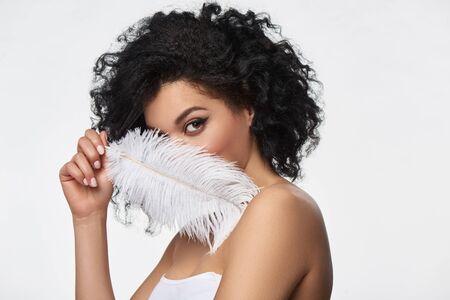 Closeup portrait of beautiful mixed race woman holding white ostrich feather, studio shot Stok Fotoğraf