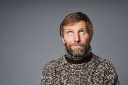 Closeup portrait of mature man in warm sweater, looking up at blank copy space, over grey studio background Stock Photo