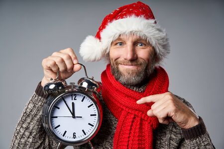 Closeup of mature man wearing Santa hat holding big alarm clock time approaching midnight, looking at camera smiling pointing at clock, over grey studio background