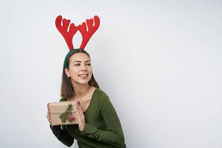 Happy girl wearing Christmas reindeer horns holding a gift box wrapped in craft paper, looking to side at blank copy space