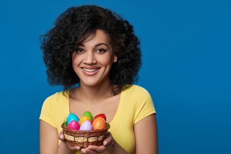 Happy woman holding a basket with colorful Easter eggs Stock Photo - 135459157