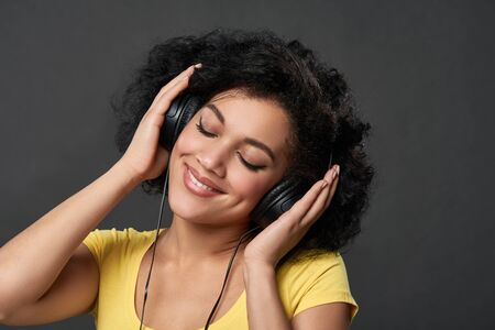 Closeup of young mixed race african woman listening music in headphones with closed eyes, studio portrait Banco de Imagens - 138177742