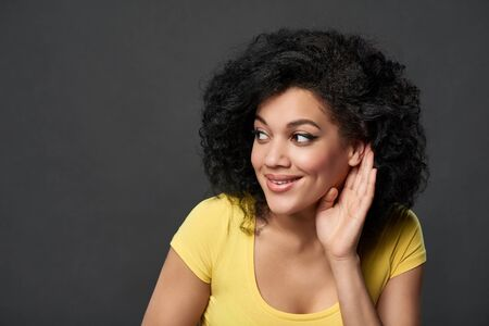 Closeup of smiling mixed race woman listening gossip with palm shielding ear looking to side at blank copy space, over grey studio background