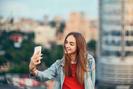 Lovely teen girl on cityscape making self portrait with her smart phone