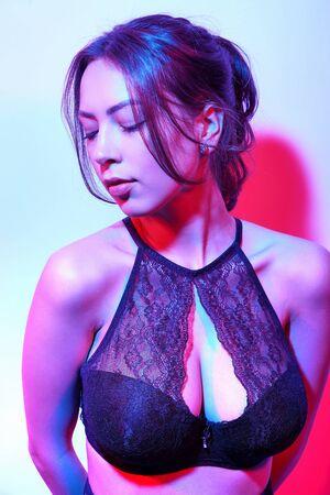 Portrait de mode beauté de la belle femme brune en lingerie noire avec néon coloré, portrait en studio Banque d'images