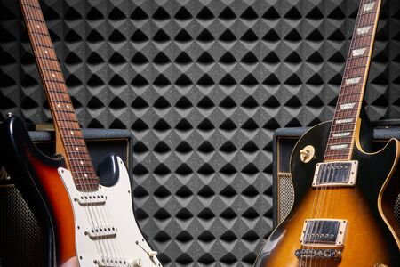 Two electric guitars leaning on Guitar Amplifier Combo over acoustic foam panel background, with copy space between