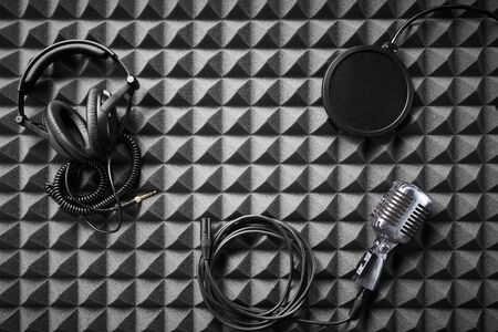 Retro microphone, professional headphones and pop-up filter lying on acoustic foam panel background, flat lay Stockfoto