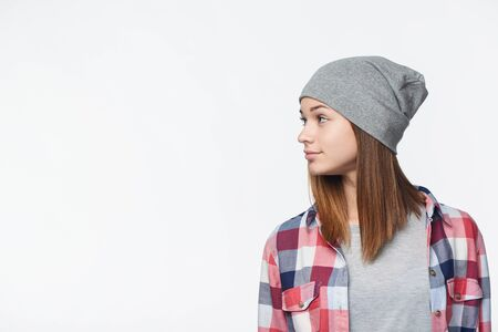 Profile of a teen girl wearing checkered shirt and beanie hat looking to side at blank copy space , studio portrait Banque d'images