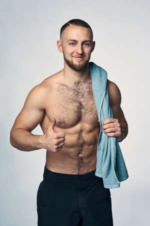 Muscular sporty shirtless man standing with towel over shoulder looking at camera gesturing thumb up