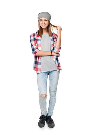 Smiling relaxed teen girl standing in full length, looking at camera, studio portrait Stock Photo