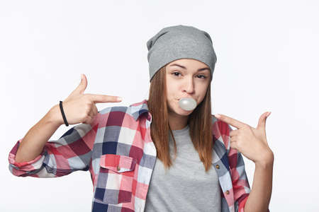 Closeup of cheeky teen girl blowing bubblegum and pointing at it, looking at camera, studio portrait