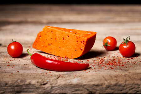 Red gourmet cheese with tomatos and parika on rough wooden planks