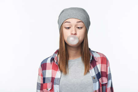 Funny portrait of teen girl blowing bubblegum and looking squinting at bubble, studio portrait over white background, isolated
