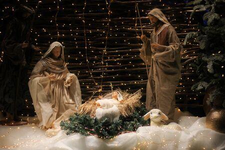 Scène de crèche de Noël avec des personnages dont Jésus, Marie, Joseph, des moutons et des mages.