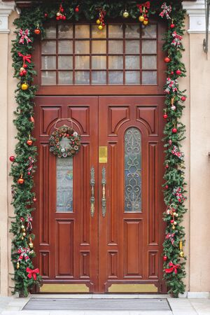 Front door with a Christmas wreath. Christmas decorations
