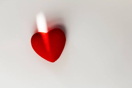 Decorative red heart on a white background with sun rays and shadow. Space for your text Foto de archivo - 138047601