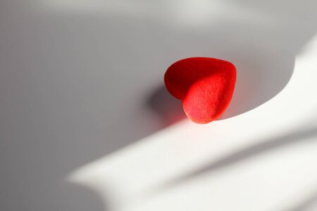 Decorative red heart on a white background with sun rays and shadow. Space for your text Foto de archivo - 138047721
