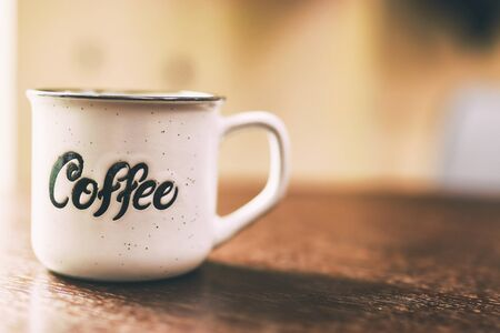 Enamel white metal mug with inscription coffee on wooden table on blurred background. White cup of coffee on a dark background. Place for text or advertising
