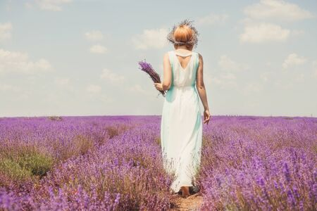Woman on the lavender field. Woman in white dress and   hat  back view. Goes on lavender rows. girl in white dress and white hat is standing in the lavender field. Soft focus