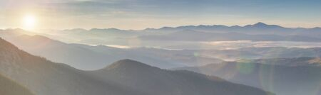 Panorama alpine landscape of the mountain peaks and valleys covered in fog at dawn. Spring landscape mountains and colorful forest on background sunrise.