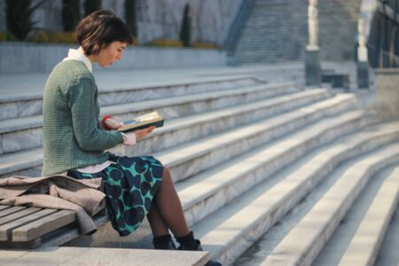 Young female student is  reads book on stairs. Full-length lifestyle portrait. A young european woman  sits on the steps  university and preparing for exams.