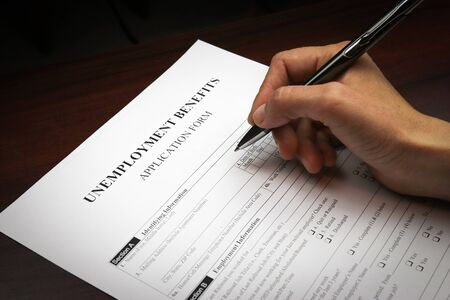 Close-up of a person's hand filing social security benefits application form.