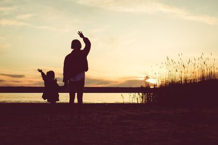 Silhouette of happy mother and little daughter at sunset. Back view of mother and young daughter standing with raised up hands enjoying sunset  view