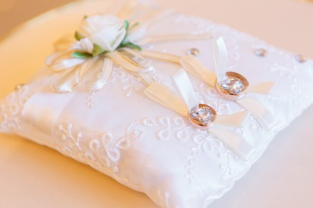 golden wedding rings on small white leather cushion Imagens