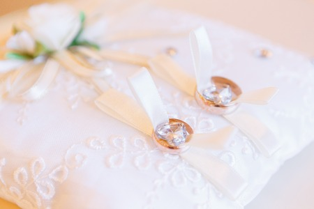 golden wedding rings on small white leather cushion 写真素材
