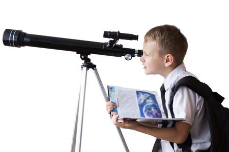 El colegial mirando a través de un telescopio sobre un fondo blanco.