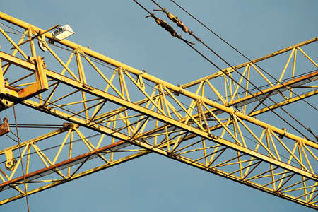 Yellow construction tower crane close-up on sky background