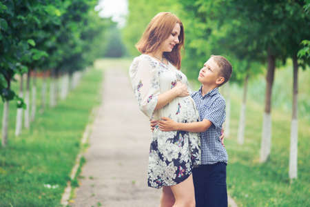 Cute pregnant woman in lace tunic hugs her son in the summer park
