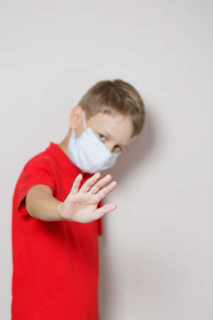 teenager with blond hair in a red T-shirt and a medical mask gets scared and repels the virus with his hand