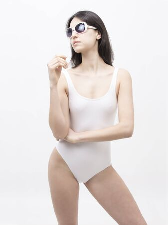 Thin model of dark hair in white swimsuit