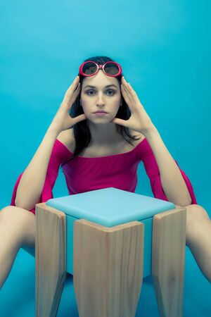 stool: Young woman in red sunglasses and a modern wooden bench