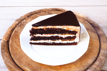 Close up of caramel chocolate banana cake on a white plate with wooden board.