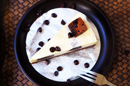 Top view of brownie cheesecake in a black plate on wooden background. Banco de Imagens